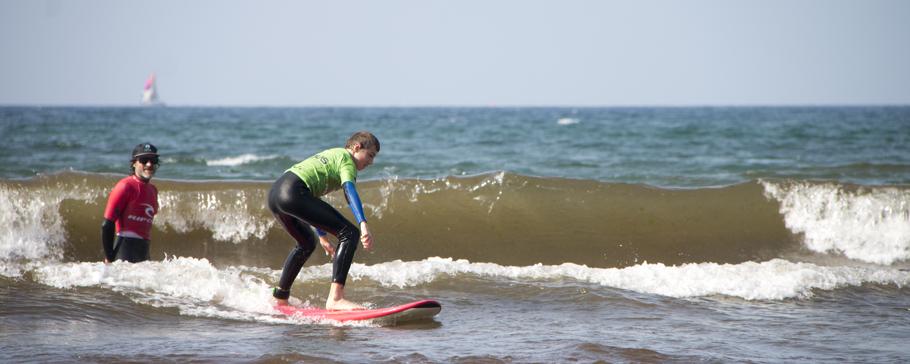 Escuela de surf. Un chico surfea y el monitor le indica qué hacer