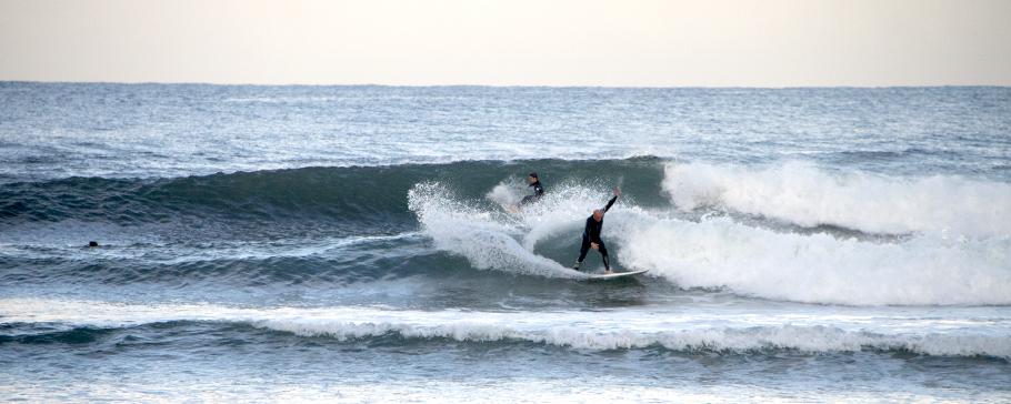Surfista haciendo una maniobra. Sesión de surf en Gijón.
